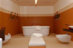 zentralperspektivisch aufgenommenes Badezimmer mit der Wanne im Hintergrund und links und rechts Waschbecken, Toilette und Bidet