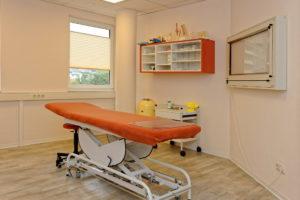 eine höhenverstellbare Liege mit orangem Bezug steht inmitten eines Behandlungszimmers