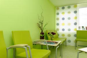 Wartezimmer einer Arztpraxis mit grünen Stühlen vor einer hellgrünen Wand
