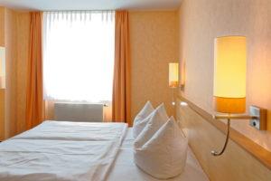 Hotelbett mit frischer Wäsche in einem frisch renovierten Raum