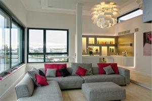 Wohnzimmer mit Bar und Wohnlandschaft über den Dächern von Rostock