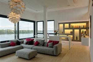 ein Wohnzimmer mit einer hinterleuchteten Bar und einem frei stehenden Tresen aus Corian und einer Aussicht über die Warnow