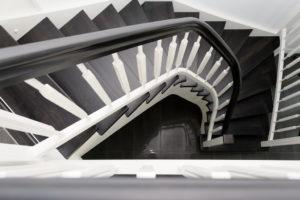 das Bild zeigt eine Treppe aus schwarzer Wenge und weißem Geländer, fotografiert von oben