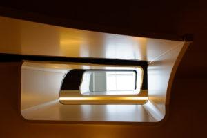 das Bild zeigt eine Betontreppe mit Holzgeländer von unten durch das Treppenauge fotografiert