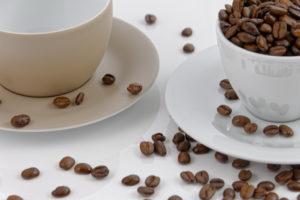 das Bild zeigt zwei angeschnittene Kaffetassen, gefüllt mit Kaffeebohnen, die sich um sie verteilen
