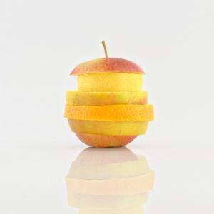 das Bild zeigt sich spiegelnde Scheiben von Obst gestapelt zu einem Apfel vor weißem Hintergrund
