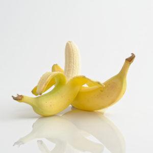 das Bild zeigt zwei Bananen, die sich aneinander lehnen, vor einem weißen Hintergrund