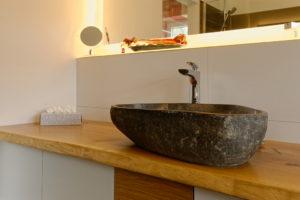das Bild zeigt ein Waschbecken aus Stein auf einer Eichenbohle