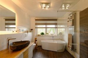 Einblick in ein Badezimmer mit klar verglaster Dusche und frei stehender Badewanne