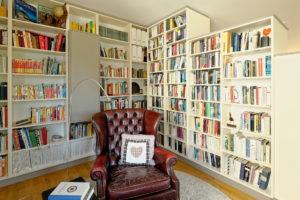 ein gemütlicher Sessel inmitten von Bücherregalen