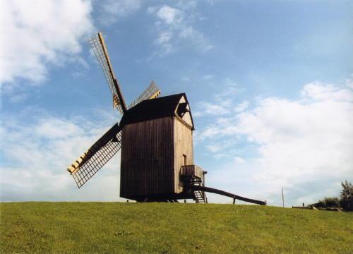 das Bild zeigt eine Bockwindmühle auf einem Hügel vor leicht bewölktem sonnigen Himmel
